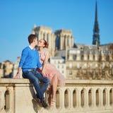 Lyckliga par som kysser nära den Notre-Dame domkyrkan i Paris arkivbild