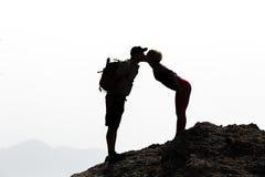 Lyckliga par som kysser på bergtoppmöte royaltyfria foton