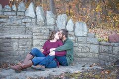 Lyckliga par som kysser vid stenväggen royaltyfri fotografi