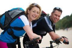 Lyckliga par som ler med deras cyklar Arkivbilder