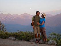 Lyckliga par som ler och kramar vid berg Arkivfoto