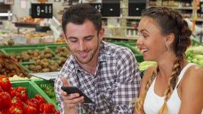Lyckliga par som ler till kameran på livsmedellagret stock video