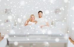 Lyckliga par som ligger i hemmastadd och hållande ögonen på tv för säng Arkivfoto