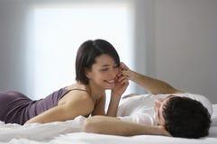 Lyckliga par som ligger i säng Arkivfoto