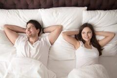 Lyckliga par som ligger i säng efter wakeup i morgonen Royaltyfria Foton
