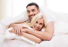 Lyckliga par som ligger i säng och hemma kramar Royaltyfri Foto