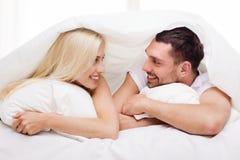 Lyckliga par som ligger i säng och hemma talar Royaltyfria Foton