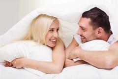 Lyckliga par som ligger i säng och hemma talar Fotografering för Bildbyråer