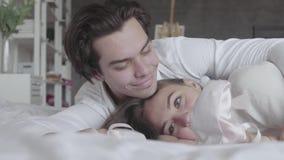 Lyckliga par som ligger i sängen som spelar med rosa barns pointenärbild Den unga familjen som väntar på a, behandla som ett barn arkivfilmer