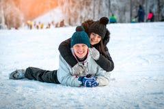 Lyckliga par som ligger i snön Fotografering för Bildbyråer