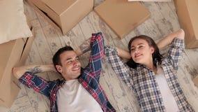 Lyckliga par som ligger på golvet i en ny lägenhet arkivfilmer
