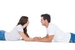 Lyckliga par som ligger på golvet som till varandra ser och rymmer händer Royaltyfri Fotografi