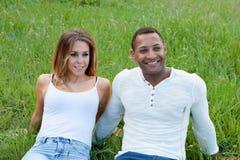Lyckliga par som ligger på gräset i fältet Royaltyfri Fotografi