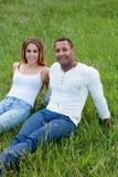 Lyckliga par som ligger på gräset i fältet Fotografering för Bildbyråer