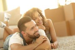 Lyckliga par som ligger på mattan på den suddiga bakgrunden Royaltyfria Bilder