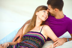 Lyckliga par som ligger på sand Arkivbilder