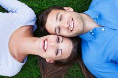 Lyckliga par som ligger på gräs Arkivbild