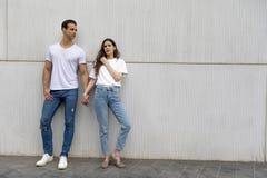 Lyckliga par som lutar mot väggen som rymmer händer som bär tillfällig kläder i en ljus dag fotografering för bildbyråer
