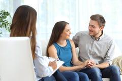 Lyckliga par som lyssnar till förbindelselägerledaren arkivfoton