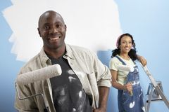 Lyckliga par som målar deras nya hus Royaltyfria Foton