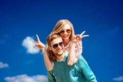 Lyckliga par som omfamnar och har gyckel under den blåa himlen fotografering för bildbyråer
