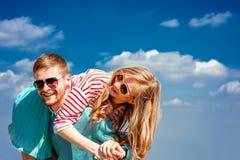 Lyckliga par som omfamnar och har gyckel under den blåa himlen royaltyfria foton