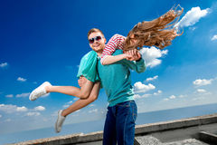 Lyckliga par som omfamnar och har gyckel under den blåa himlen royaltyfri foto
