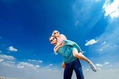 Lyckliga par som omfamnar och har gyckel under den blåa himlen arkivfoton