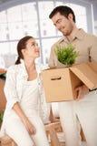 Lyckliga par som packar upp askar i ny utgångspunkt royaltyfri fotografi