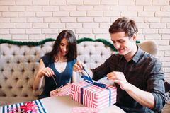 Lyckliga par som packar upp xmas-gåvor Royaltyfri Fotografi