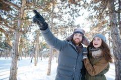 Lyckliga par som pekar och ser upp i vinter, parkerar Royaltyfri Fotografi