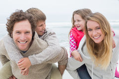 Lyckliga par som piggybacking ungar på stranden Royaltyfria Bilder