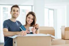 Lyckliga par som planlägger deras nya hus Royaltyfri Foto