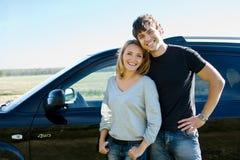 Lyckliga par som plattforer nära bilen Royaltyfria Foton