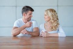 Lyckliga par som pratar över morgonkaffe arkivbild