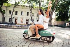 Lyckliga par som rider en sparkcykel Arkivbild