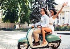 Lyckliga par som rider en sparkcykel Fotografering för Bildbyråer