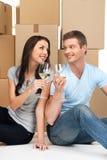 Lyckliga par som rostar champagneflöjter mot kartonger i nytt hus Arkivfoto