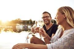 Lyckliga par som rostar exponeringsglas Arkivfoton
