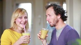 Lyckliga par som rostar och dricker fruktsmoothien lager videofilmer