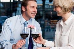 Lyckliga par som rostar rött vin Royaltyfri Bild