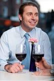 Lyckliga par som rostar rött vin Arkivbild