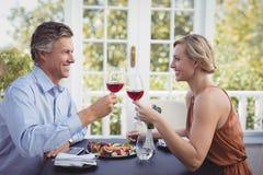 Lyckliga par som rostar vinexponeringsglas, medan ha mål Royaltyfri Foto