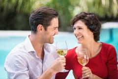 Lyckliga par som rymmer vitt vin Fotografering för Bildbyråer