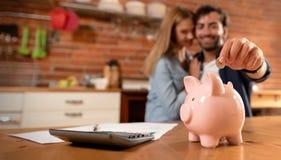 Lyckliga par som sätter in myntet i piggybank royaltyfria bilder