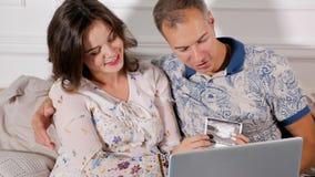 Lyckliga par som ser, behandla som ett barn bildläsning fotografering för bildbyråer