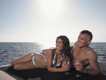 Lyckliga par som ser bort, medan ligga på yachten Arkivfoto