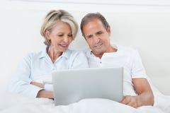 Lyckliga par som ser den digitala minnestavlan Royaltyfri Fotografi