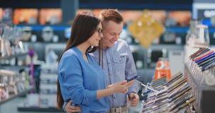 Lyckliga par som ser en ny digital kamera på en elektronik, shoppar arkivfilmer