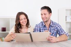 Lyckliga par som ser fotoalbumet Fotografering för Bildbyråer